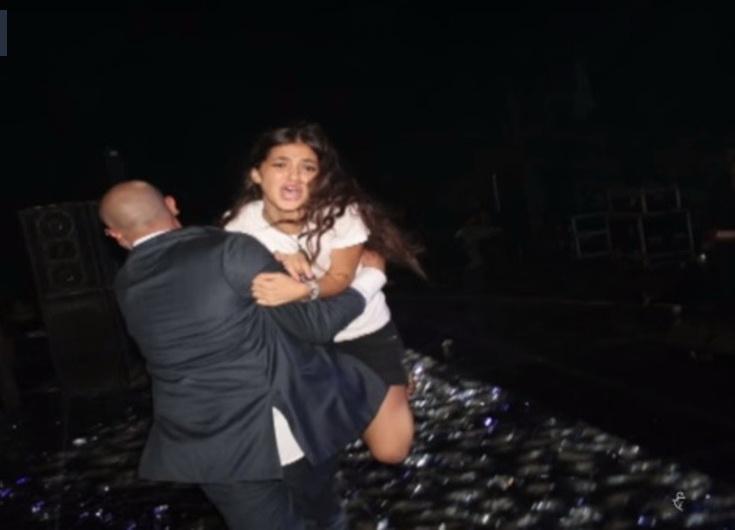 إحدى الفتيات المهووسات تحاول الوصول إلى النجم تامر حسني في إحدى حفلاته، حيث يبعدها أحد الحراس.
