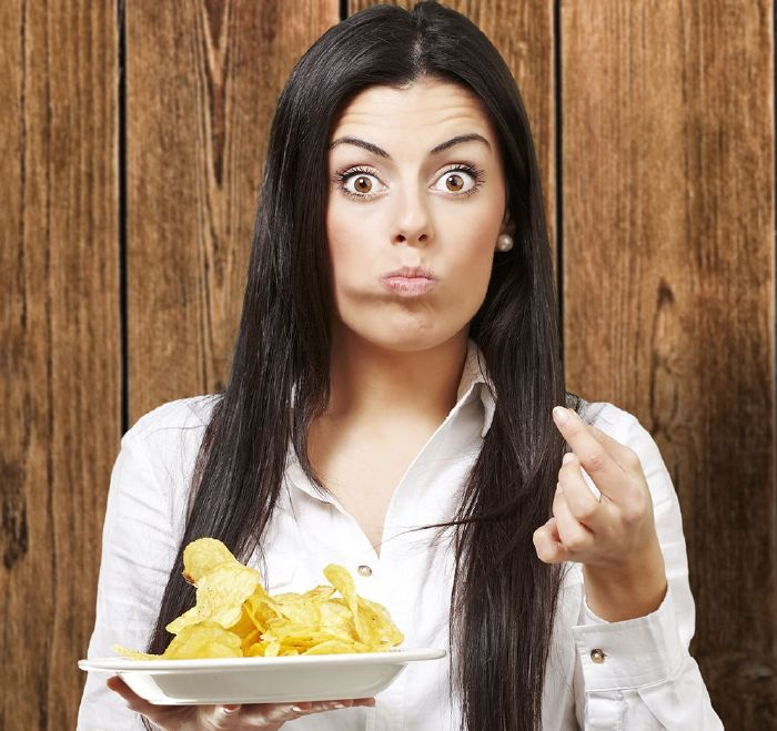 resized_surprised woman eating plate of potato chips
