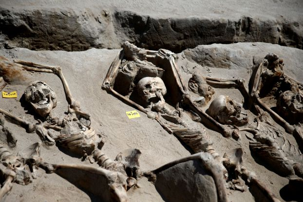 Skeletal remains, with iron shackles on their wrists, are laid in a row at the ancient Falyron Delta cemetery in Athens
