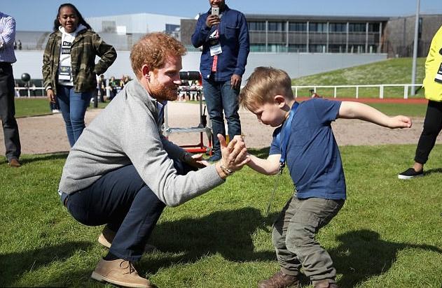 الأمير هاري يلعب مع عدد من الأطفال الصغار الذين حضروا لمتابعة المنافسات